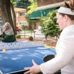 People's Center staff playing ping pong on the Temporary Table Tennis Trailer on the clinic lawn.