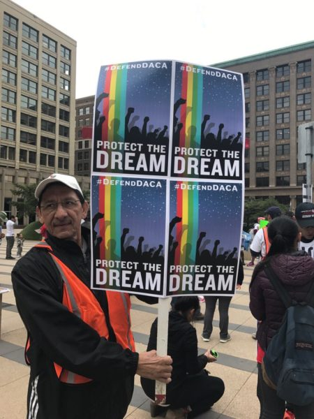 "Posters by artist Leon Wang read ""Protect the Dream"" and depict illustrations of people and a rainbow"