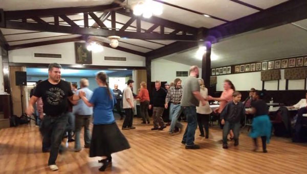 A large hall with people dancing a square dance