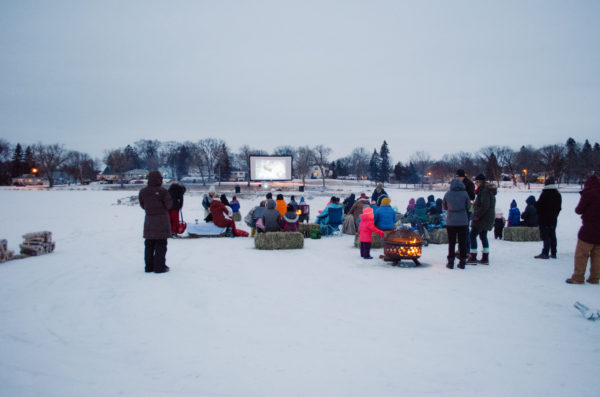 People gathered around a movie screen set up on a frozen lake