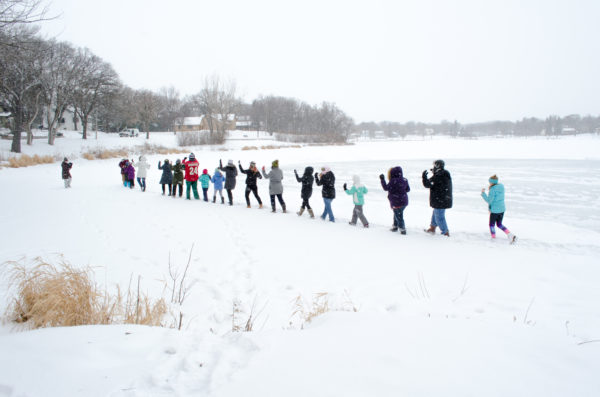 A row of people moving across a frozen lake