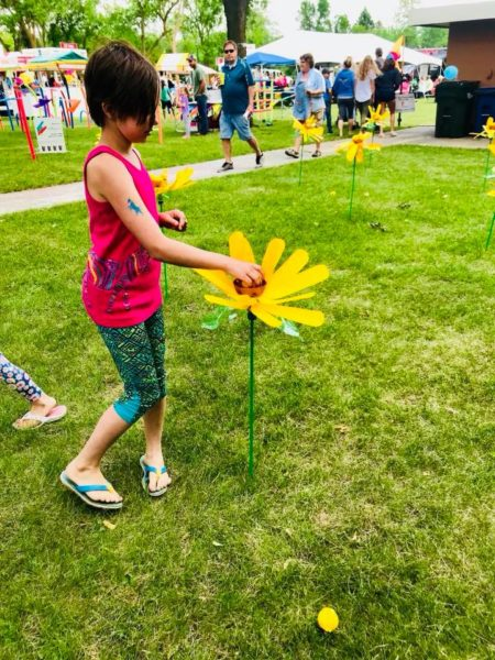 A child in a red shirt plays with a yellow flower scultpure