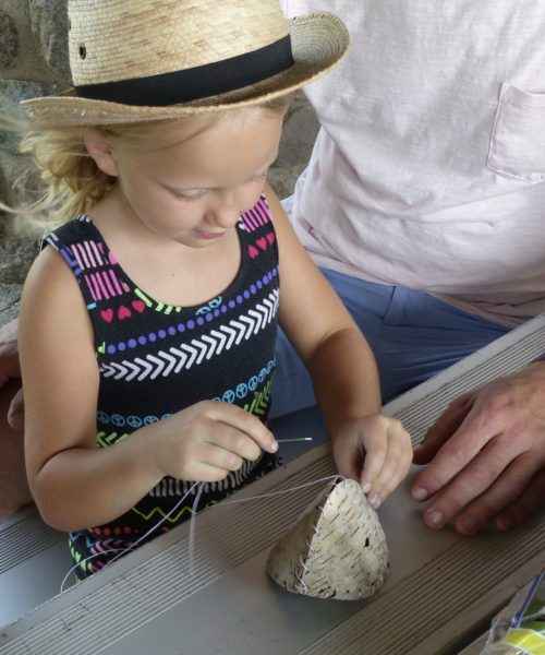 A young girl weaves a birchbark basket as part of Year of Play