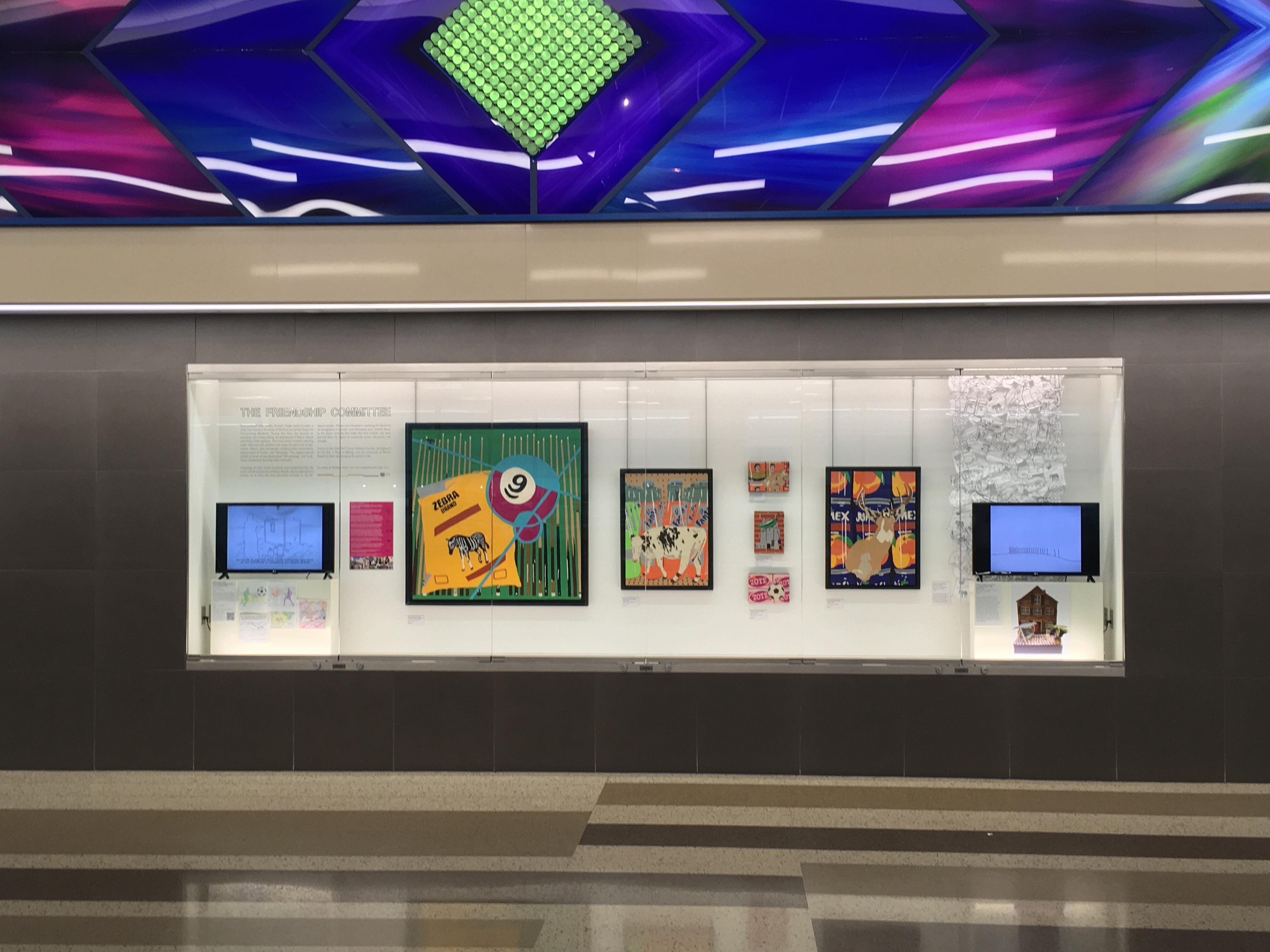 Brightly colored art by Wesley Fawcett Creigh installed in a glass case in an airport terminal