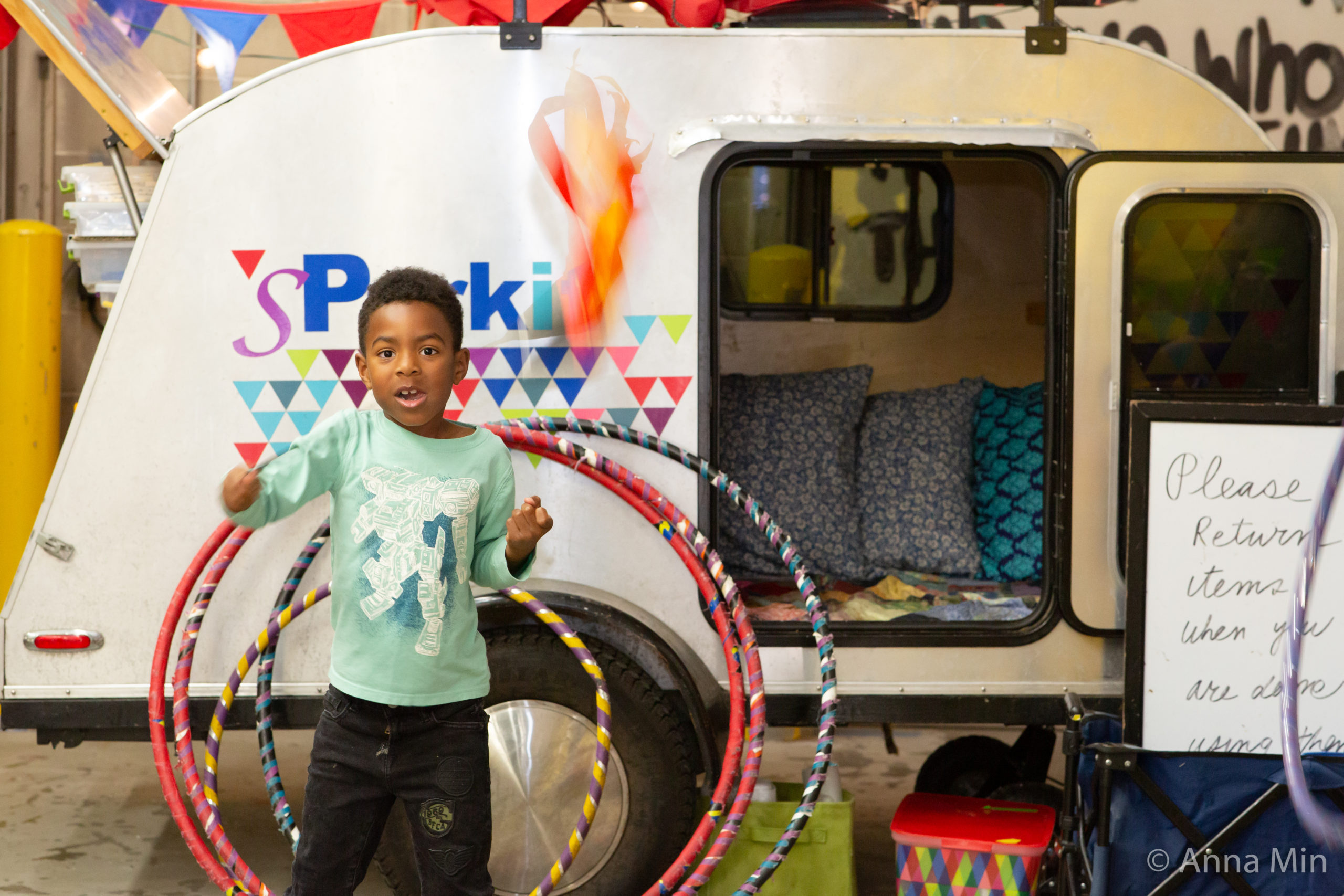 A child plays with hula hoops and fabric at the SparkIt Trailer