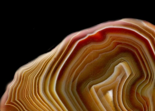 An agate stone in whorled oranges and reds