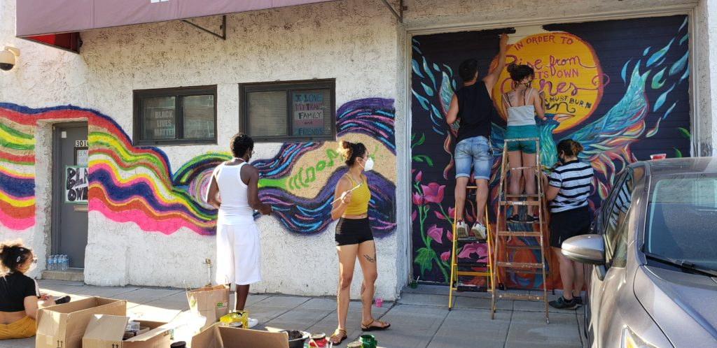 RARE Productions: People painting a colorful mural