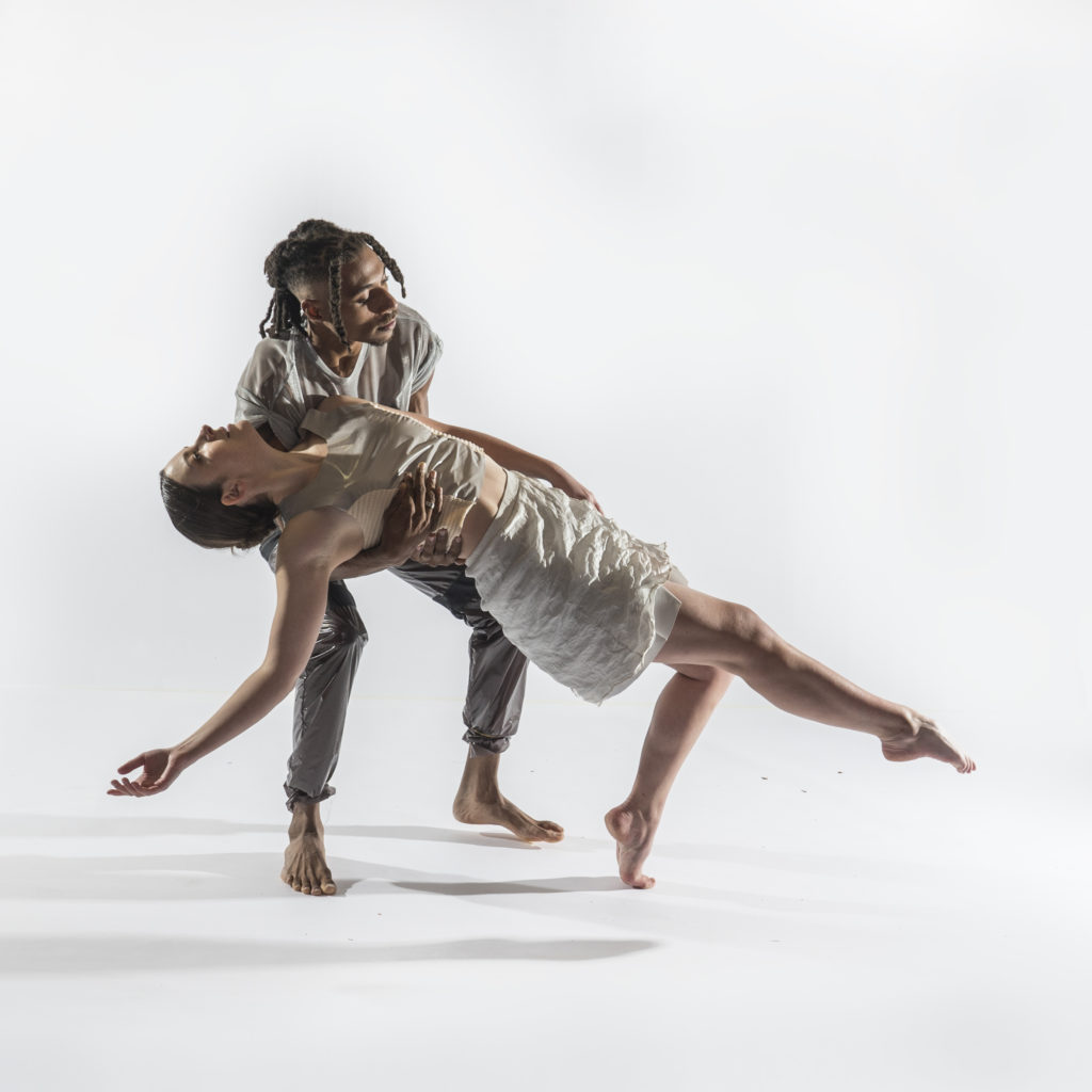 HATCH DANCE: Two dancers in white clothes, one holding up the other