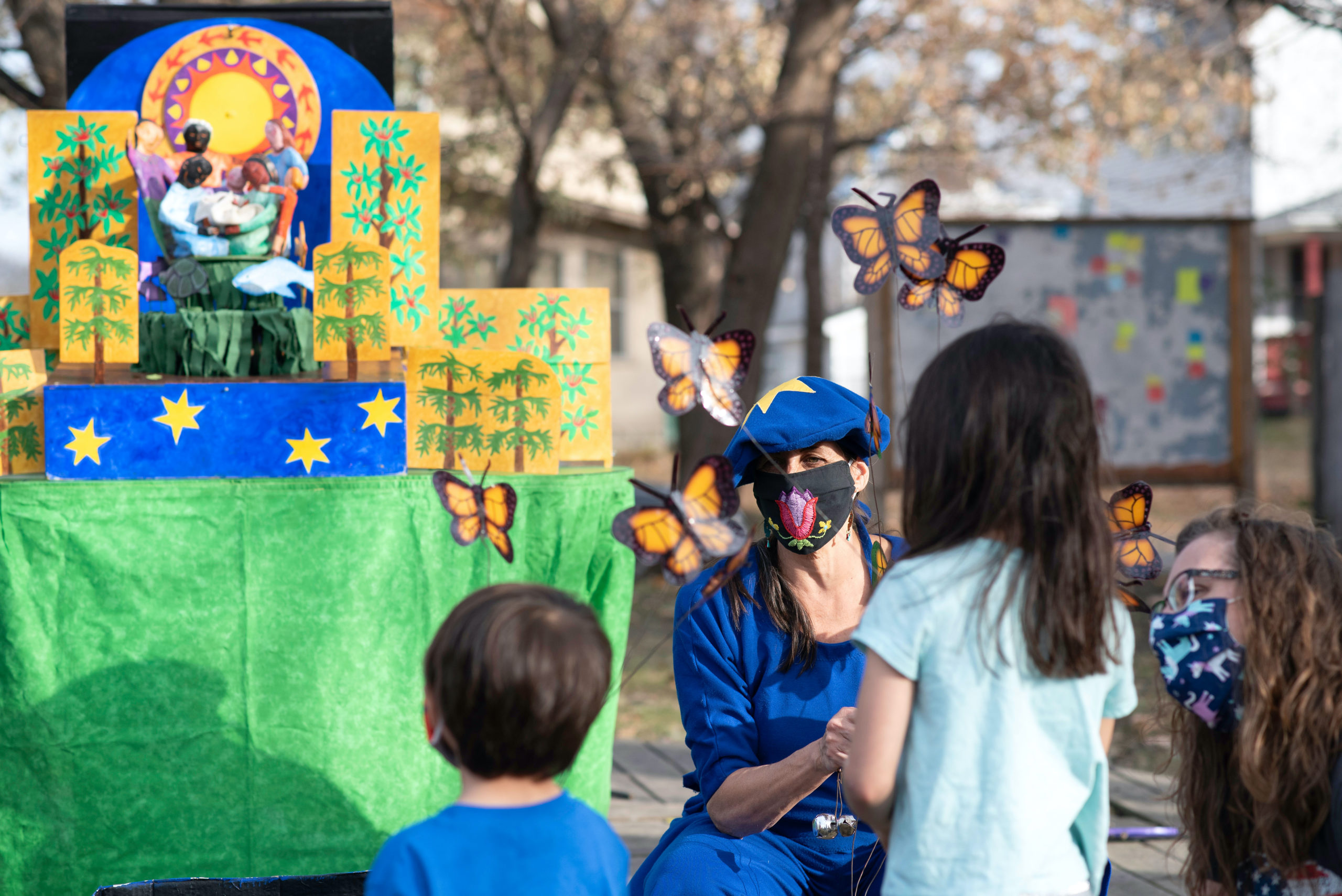 A performer in a blue mask with monarch butterfly puppets in front of a colorful set