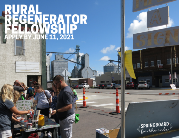 People gathered around a table making signs, standing in a parking lot with a grain elevator in the background