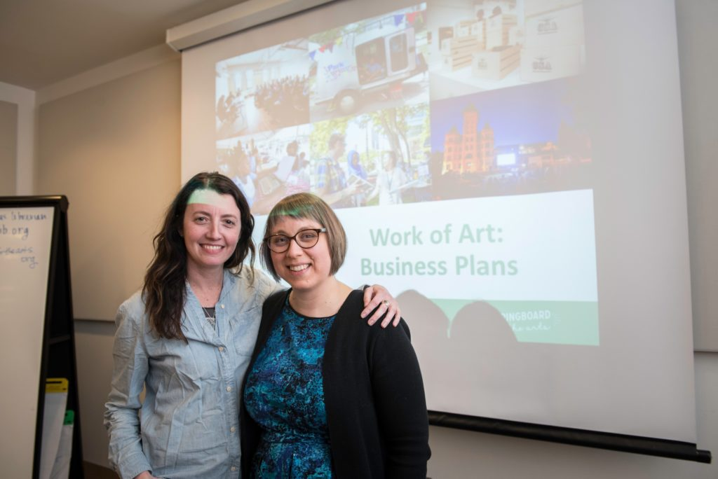 Two women stand together in front of a projection reading Work of Art: Business Plans